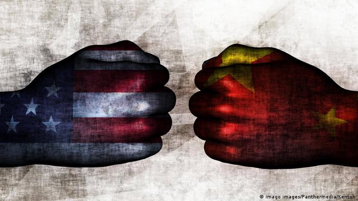 Два повернутых друг к другу кулака: один раскрашен как флаг США, второй - как флаг КНР