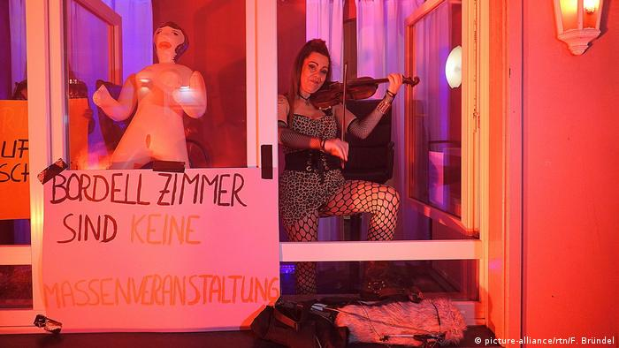 A woman plays a violin the window of a brothel in Hamburg. A poster says, 'A brothel room is not mass event.'