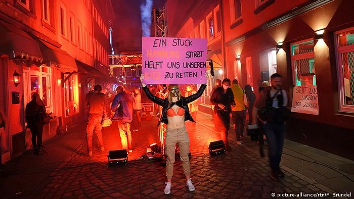 Woman in mask holding placard reading: 'A piece of Hamburg is dying, help save our Kiez'