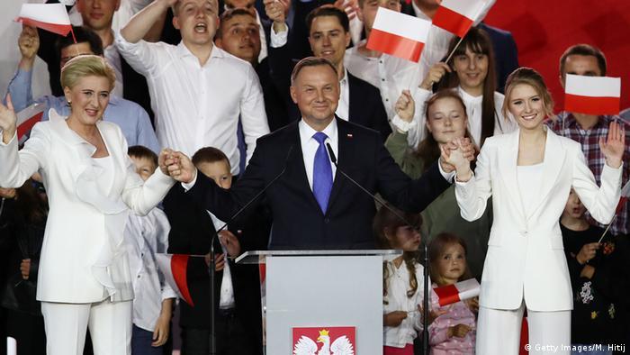Presidente polonês, Andrzej Duda, com mulher e filha no palco, durante evento de campanha