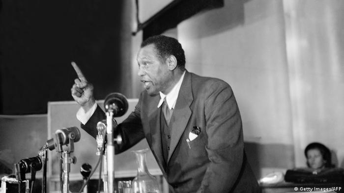 Robeson, a singer, actor and activist, speaks in front of a microphone.