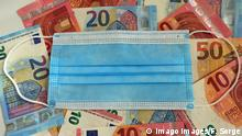 A mask sits atop a table full of euro bills (Imago Images/F. Sorge)