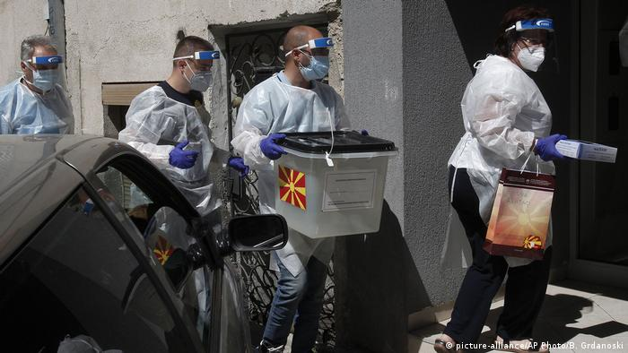 Members of a special election team visit voters under quarantine in the Macedonian capital, Skopje