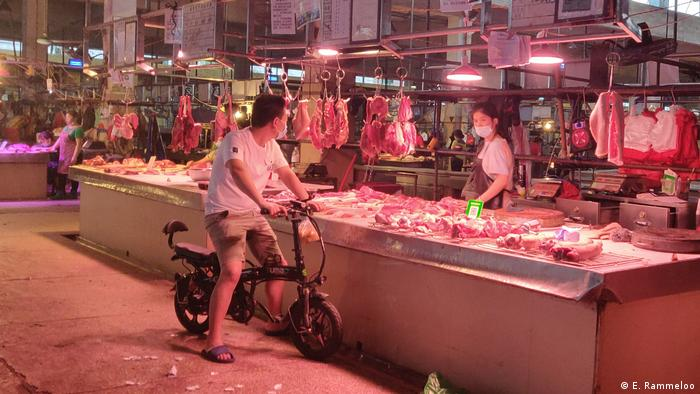 A man on a motorbike stops to buy meat at a market in Guangzhou