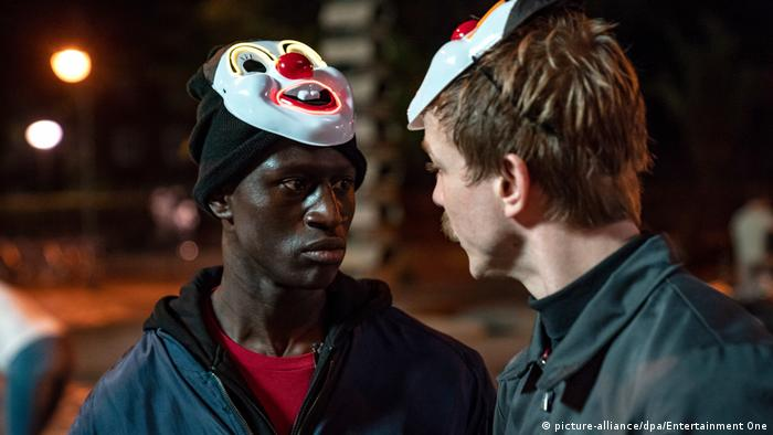Two characters from 'Berlin Alexanderplatz' face one another wearing clown masks on their heads