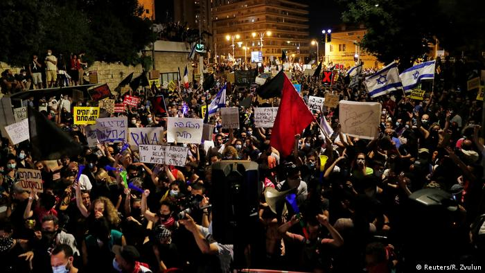 Protesters stand in a big crowd holding signs and waving flags in Jerusalem