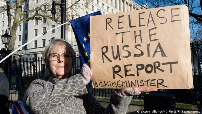 A protester outside Downing Street holding up a sign urging the release of the Russia report