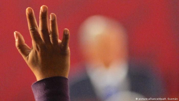 Foto de una mano frente a Andres Manuel Lopez Obrador