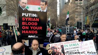 Демонстрация противников режима Асада, мужчина держит плакат Путин, сирийская кровь на твоих руках