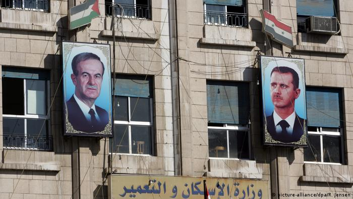 Портреты отца и сына Асадов, висящие на фасаде здания