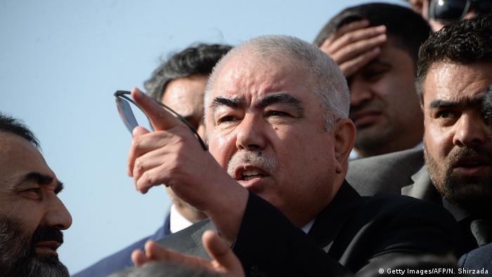 Im Zentrum Kopf eines Manns mit sehr kurzen weißen Haaren und dunklen Augenbrauen, der mit dem Zeigefinger nach vorne weist, mehrere Männer stehen hinter ihm und schauen in die Richtung, wohin er zeigt