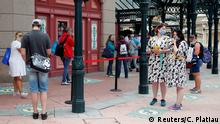 Visitors maintain social distance as they line-up at a souvenirs shop at Disneyland Paris as the theme park reopens its doors to the public in Marne-la-Vallee, near Paris