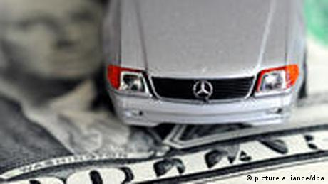 A toy Mercedes on a US dollar (picture alliance/dpa)