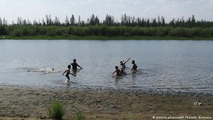 Children play in a lake in the Sakha Republic during summer heat