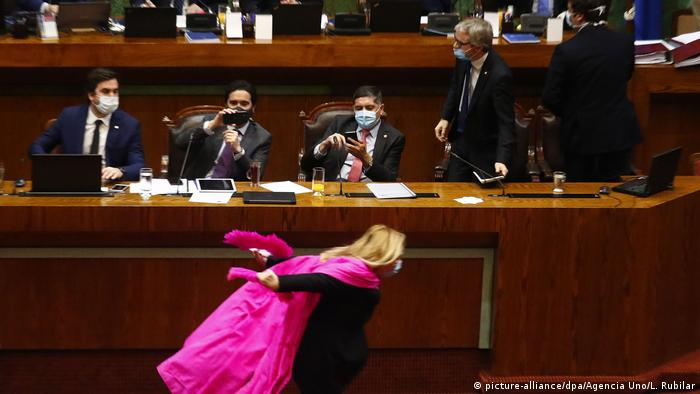 Pamela Jiles sprints in front of senior ministers in Chile wearing a pink cape (picture-alliance/dpa/Agencia Uno/L. Rubilar)