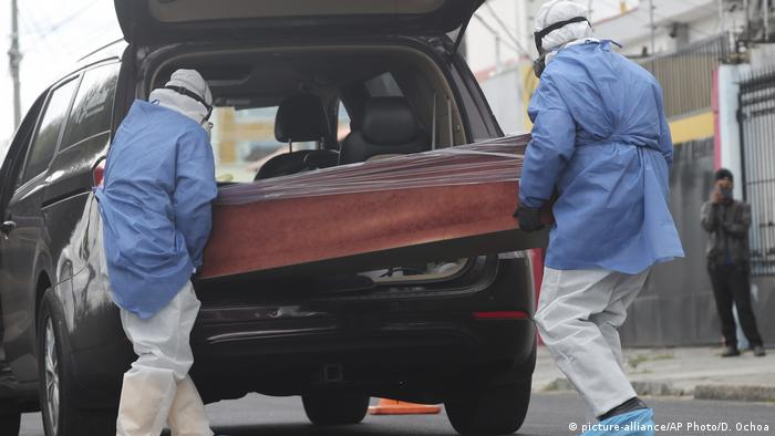 Funeral workers move the coffin with the body of a man who died inside a taxi as he was being taken to hospital in Quito (picture-alliance/AP Photo/D. Ochoa)
