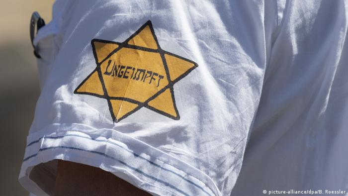 A yellow star with the words 'unvaccinated' on the arm of a protest