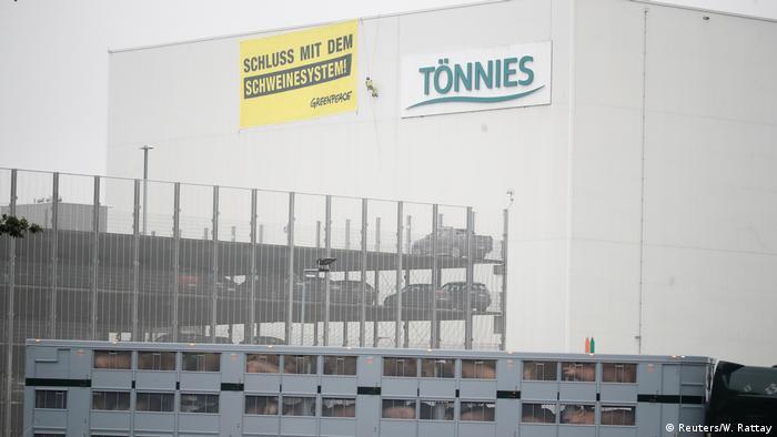Ein Lastwagen voller Schweine kommt in Deutschlands größtem Schlachthof Tönnies an, während ein Greenpeace-Aktivist ein Transparent mit der Aufschrift Schluss mit dem Schweinesystem entrollt