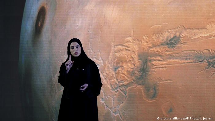 Sarah al-Amiri stands in front of a projection of Mars and talks about the Hope mission