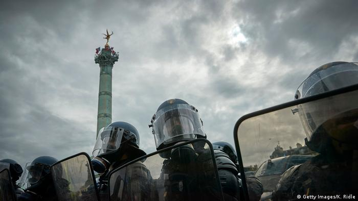 French riot police wearing gas masks look towards anti-government demonstrators in Paris