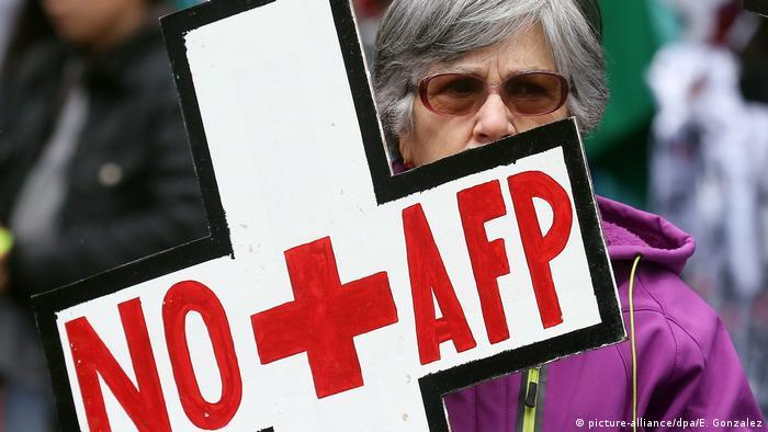 Una mujer chilena porta un cartel que dice: No + AFP.