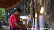A woman lights a candle at the monument to the victims of El Mozote massacre, executed by the army during El Salvador's 1980-1992 civil war, during a commemoration in El Mozote, 200 km east of San Salvador, on December 7, 2019. - Salvadoreans are commemorating the 38th anniversary of the massacre with the hope that the soldiers accused of the infamous event in which according to official figures 986 people, including 558 children, were killed, are punished. More than 75,000 people were killed or went missing during the country's civil war. (Photo by MARVIN RECINOS / AFP) (Photo by MARVIN RECINOS/AFP via Getty Images)
