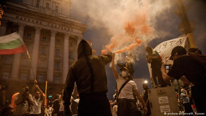 A man in a hoodie sprays smoke in the air in front of a building in Sofia, Bulgaria (picture-alliance/H. Russev)