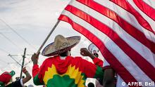 ST. PAUL, MN - JULY 08: A man holds up the U.S. flag as members of the Oromo community march in protest over the death of musician and revolutionary Hachalu Hundessa on July 8, 2020 in St. Paul, Minnesota. The protesters called for Internet service to be restored in Ethiopia after it was shut down on June 30. Community leaders also urged the U.S. to aid in the release of Oromian and American prisoners. This latest uprising follows the death of Hachalu Hundessa, who was murdered in Ethiopia on June 29. His death has sparked ongoing protests around the world. Brandon Bell/Getty Images/AFP