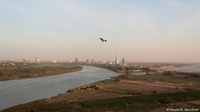 A bird flies over the confluence of the Blue Nile and White Nile with buildings of Khartoum in the background