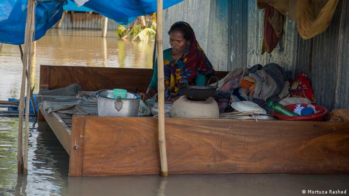 A woman sits on a bed covered in household items. The area is covered in water