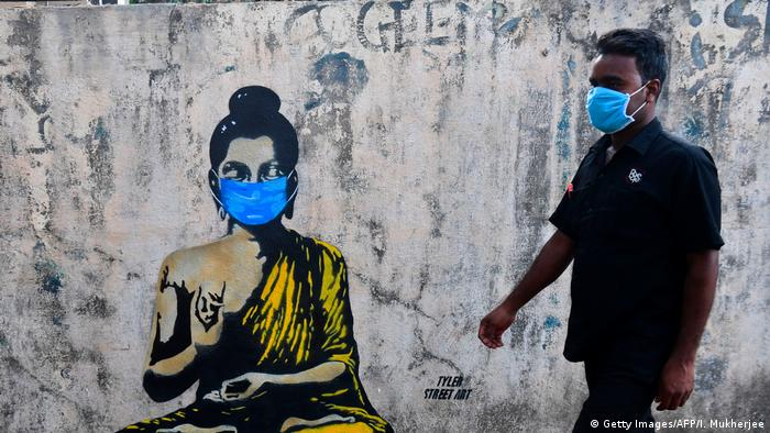 A graffiti of the Buddha wearing a blue facemask with a person walking next to him wearing the same facemask.