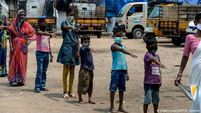 Lockdown in Indien: Menschen auf der Straße stehen hintereinander und strecken ihren rechten Arm aus.