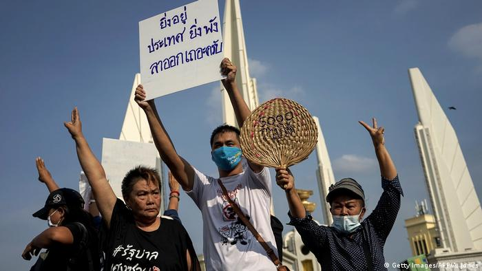 Protesters in Bangkok hold a sign that reads, The longer you stay, the more devastation to the country, please resign
