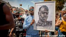 PERSAN, FRANCE - JULY 18: A Black Lives Matter protestor holds a portrait of Adama Traoré during demonstrations to commemorate the fourth anniversary of his death, when three police officers used the weight of their bodies to detain him in 2016, on July 18, 2020 in Persan, France. Protests have taken place across France in the wake of the death of African American George Floyd at the hands of police officers in Minneapolis, USA, with the French government under increased pressure to address long running accusations of racism and police brutality towards black and ethnic minority groups. (Photo by Kiran Ridley/Getty Images)