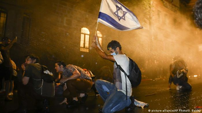 A protester holds an Israeli flag above his head while being sprayed by a water cannon