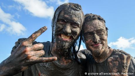 Two fans covered in mud at the Wacken outdoor festival.