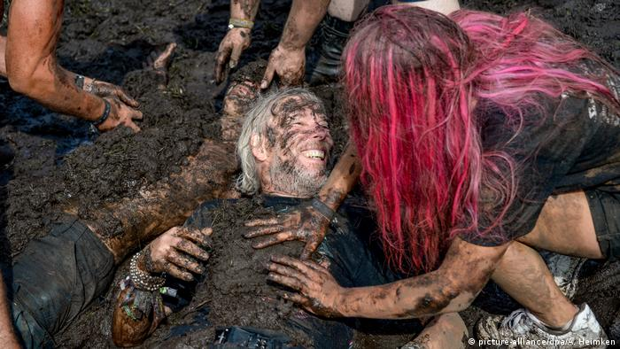 A person covered in mud smiles as a red-haired friend kneels down next to them