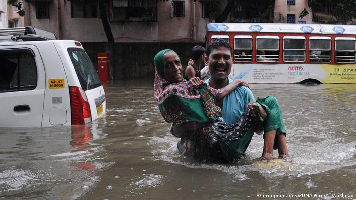 A man carries a woman through floodwaters in India