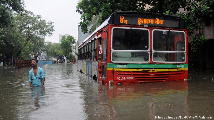 A man wades through floodwaters next to a submerged bus