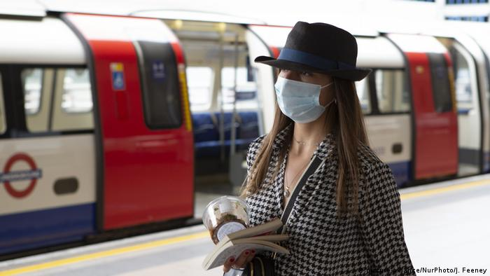Женщина в маске на перроне вокзала в Лондоне