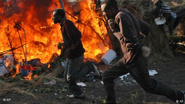 Displaced Somalis run past a burning tent during the attacks against immigrants in South Africa in 2008.