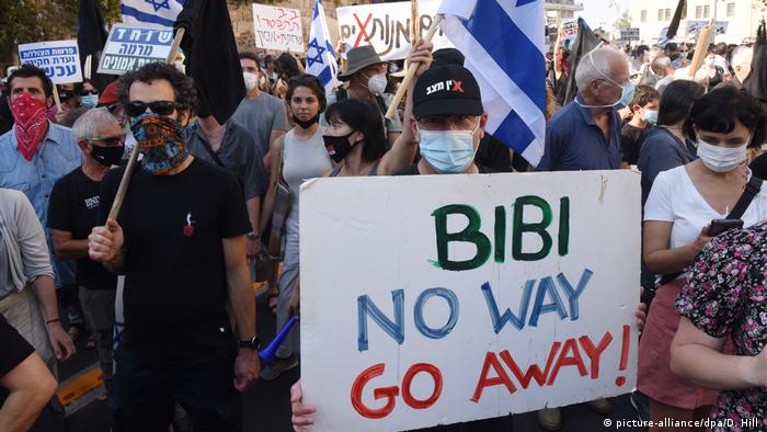 Protesters hold up a sign reading 'Bibi no way go away'