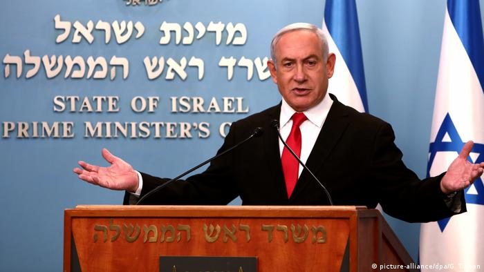 Benjamin Netanyahu speaks at a press conference from behind a podium
