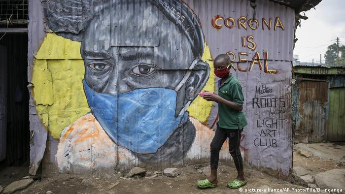 A boy wearing a face mask walks past a mural of a woman with a face mask in a Nairobi slum