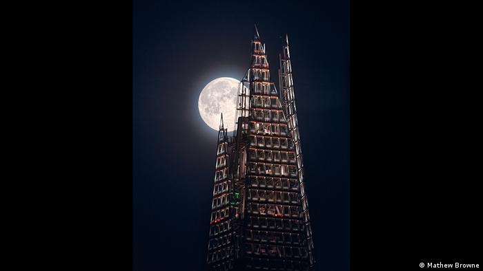 The bright orb of the moon peeks out from the jagged top of the Shard skyscraper. (Photo: Mathew Browne).