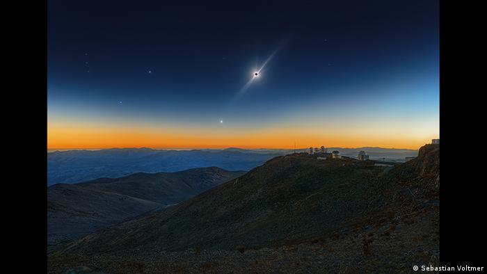 Die Sonne ist vom Mond verdeckt, strahlt darüber hinaus. Der Himmel ist dunkel, am Horizont ist ein rötlicher Streifen zu sehen, ein Stern leuchtet hell neben der Sonne (Foto: Sebastian Voltmer).