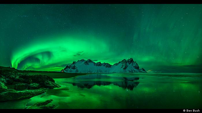 Green light swirls in this photo of arctic waters and snow-capped rock formations (Photo: Ben Bush ).