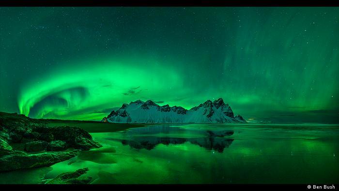 Nachthimmel mit Wasser im Vordergrund, im Hintergrund schneebedeckte Berge, am Himmel wabenartige neongrüne Nordlichter (Foto: Ben Bush ).