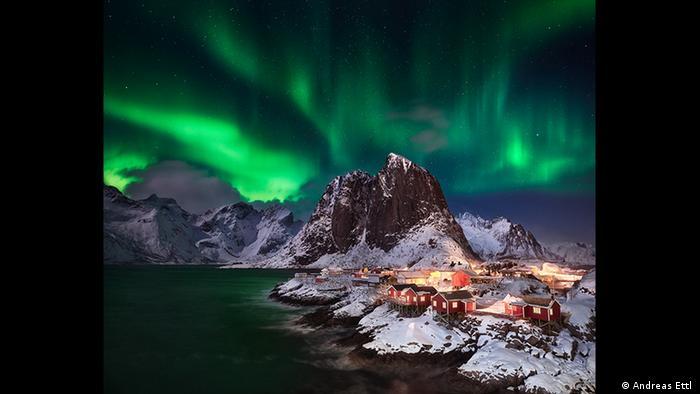 Nachtaufnahme einer kleinen Küstensiedlung mit roten Häusern und schneebedeckten Bergen. Am Himmel sind flirrende grüne Lichter zu sehen (Foto: Andreas Ettl ).