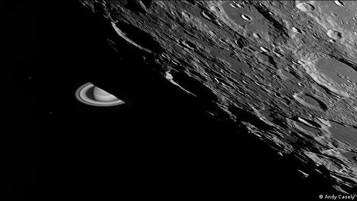 Schwarz-weiß Fotografie der Mondoberfläche mit diversen Kratern, dahinter taucht im Anschnitt der Planet Saturn mit Ringen auf (Foto: Andy Casely).